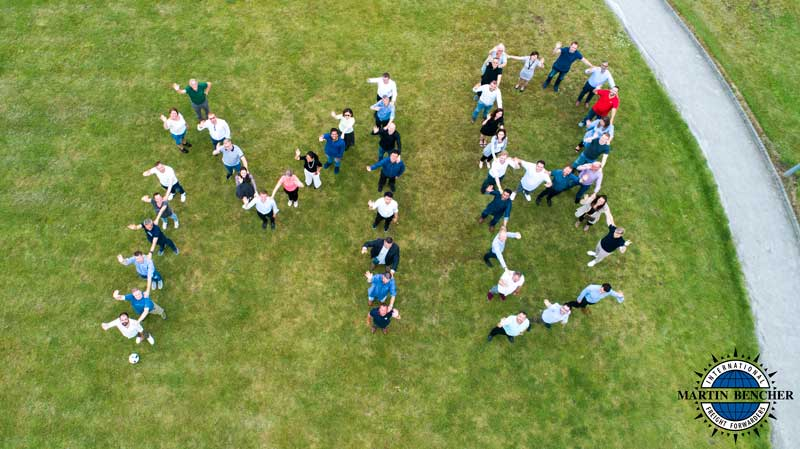 Martin Bencher Employees forming an MB on a field